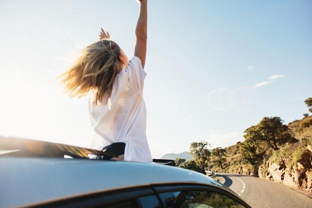 Frau im auto road trip winkt lächelnd aus dem fenster. Kostenlose Fotos