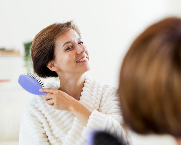 Frau im bademantel bürstet ihr haar im spiegel Kostenlose Fotos