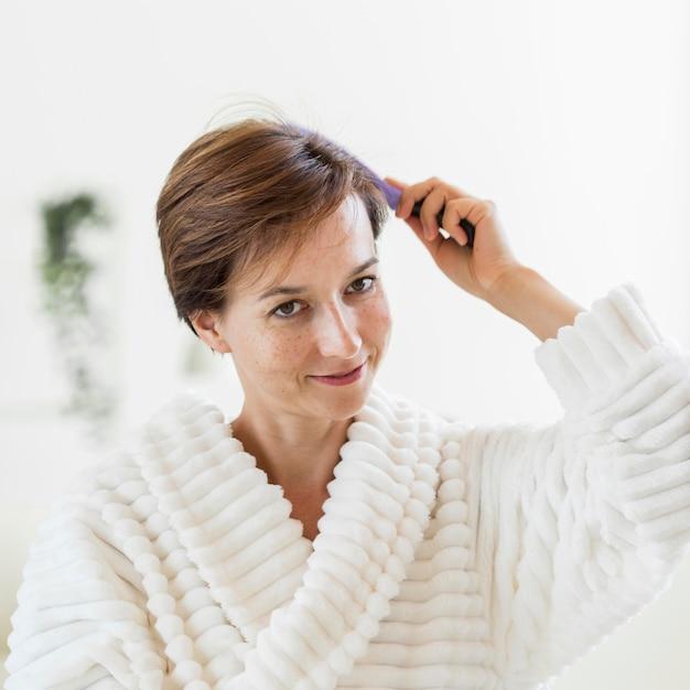 Frau im bademantel bürstet ihr haar und lächelt Kostenlose Fotos