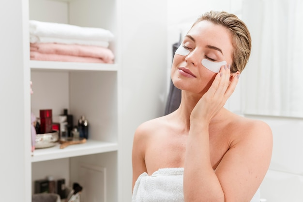 Frau im badezimmer mit behandlung unter augentaschen Premium Fotos