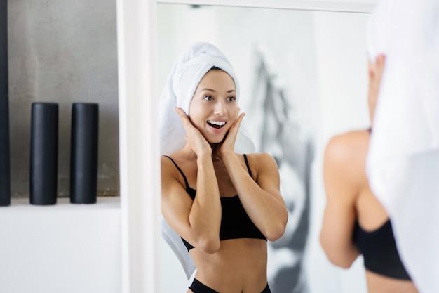 Frau im badezimmer mit einem handtuch auf dem kopf vor einem spiegel. Kostenlose Fotos