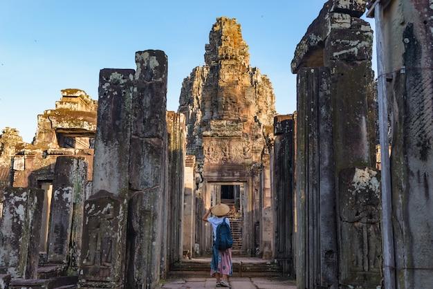 Frau im bayon tempel, der steingesichter betrachtet Premium Fotos