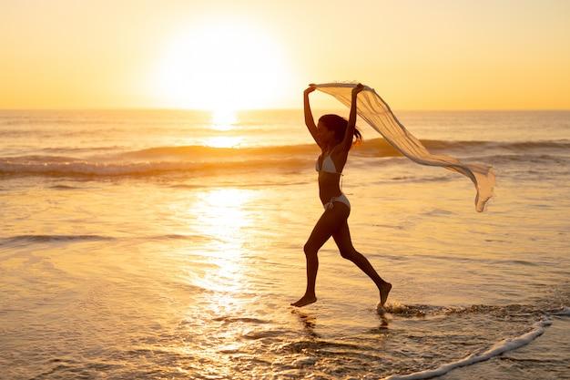Frau im bikini läuft mit schal am strand Kostenlose Fotos