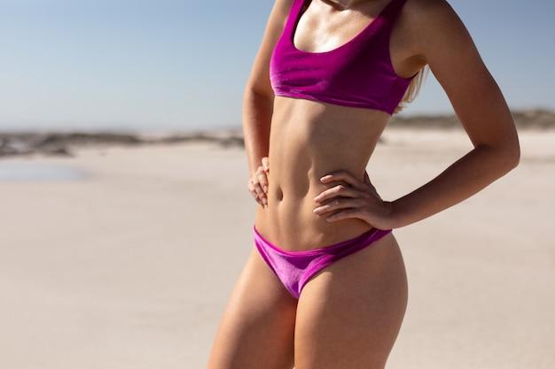 Frau im bikini mit den händen auf der hüfte, die am strand im sonnenschein steht Kostenlose Fotos