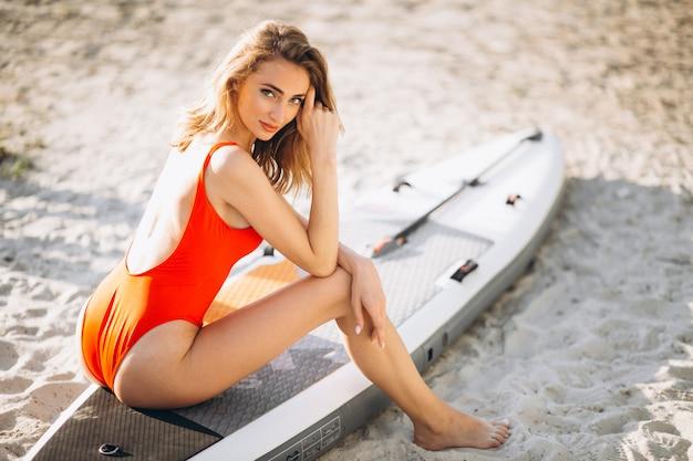 Frau im bikini mit einem surfenden brett an ihm strand Kostenlose Fotos