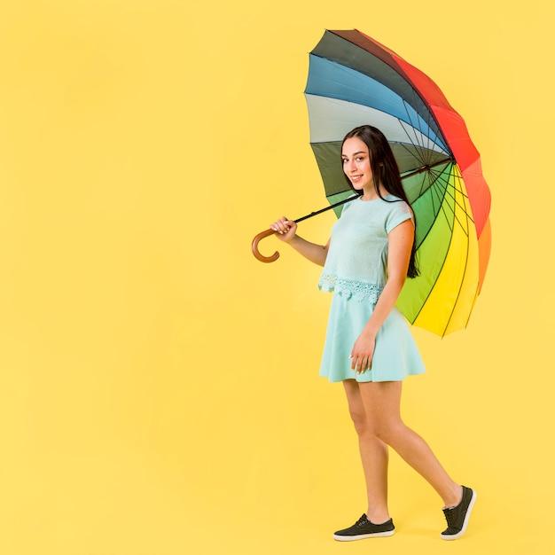 Frau im blau mit regenbogenregenschirm Kostenlose Fotos
