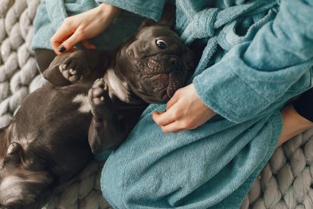 Frau im blauen bademantel mit schwarzer bulldogge Kostenlose Fotos