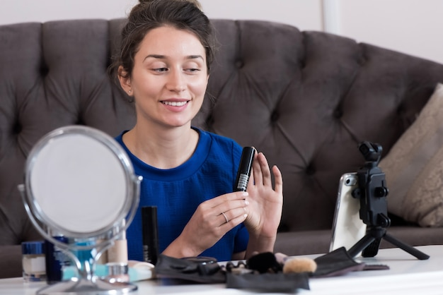 Frau im blauen kleid, das ein make-up vlog darstellt Premium Fotos