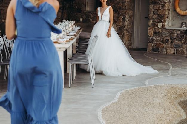 Frau im blauen kleid geht in richtung zur braut im noblen hochzeitskleid Kostenlose Fotos