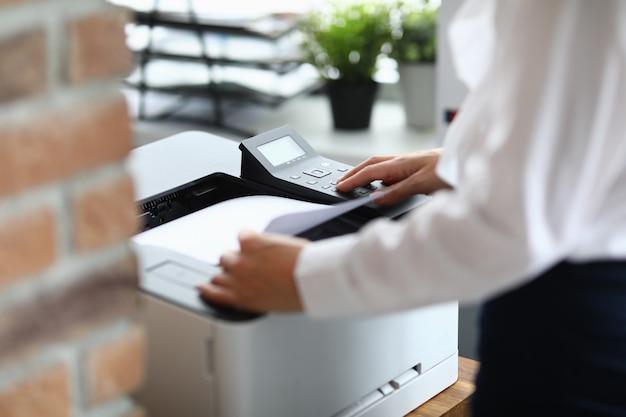 Frau im büro druckt dokumente auf drucker Premium Fotos