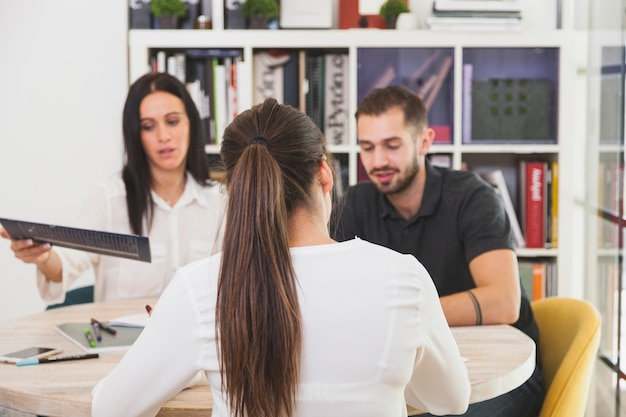 Frau im büro sitzen und reden Kostenlose Fotos