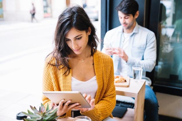 Frau im café, das an tablette arbeitet Kostenlose Fotos