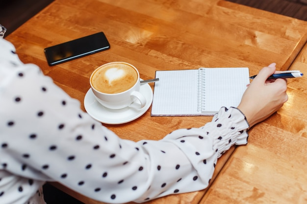 Frau im café, das in notizbuch sitzt und schreibt Premium Fotos