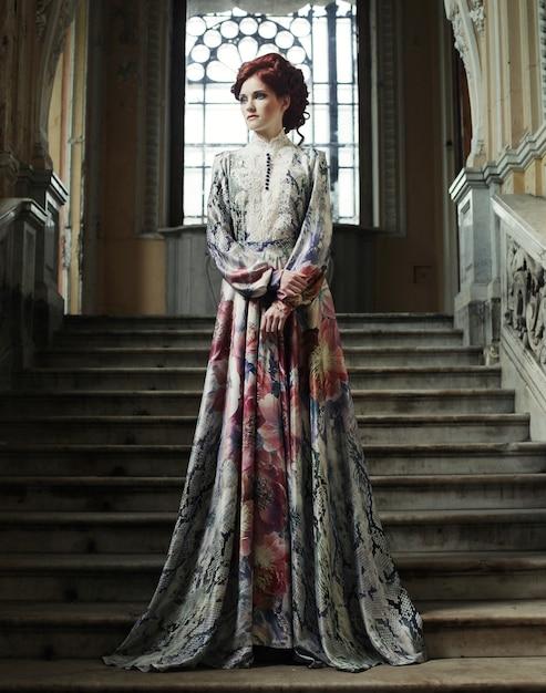 Frau im eleganten kleid, das auf treppen aufwirft Premium Fotos