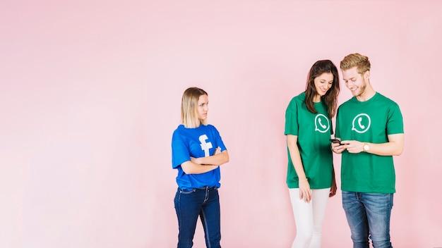 Frau im facebook-t-shirt, das glückliches paar unter verwendung des mobiltelefons betrachtet Kostenlose Fotos