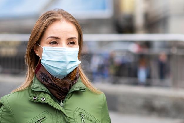 Frau im freien, die eine schutzmaske trägt Kostenlose Fotos