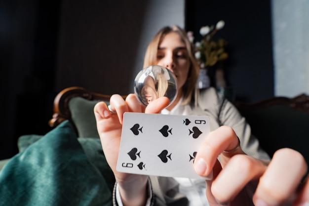 Frau im geschäftsanzug, der kristallkugel und sechs spaten in ihren händen hält Kostenlose Fotos