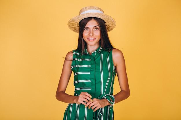 Frau im grünen kleid und im hut auf gelbem hintergrund Kostenlose Fotos