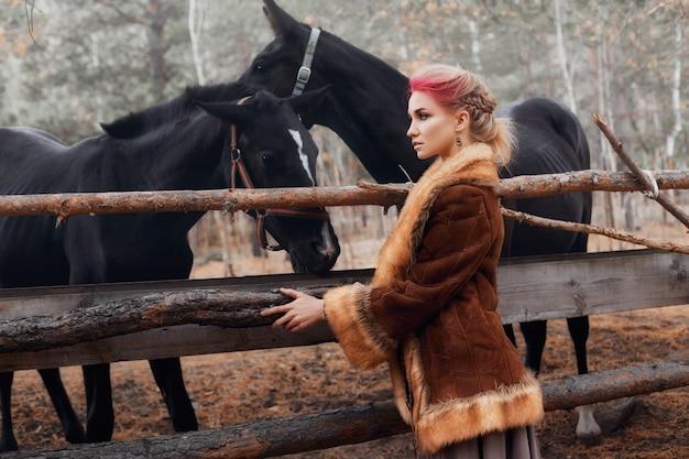 Frau im herbstwald mit pferden Premium Fotos