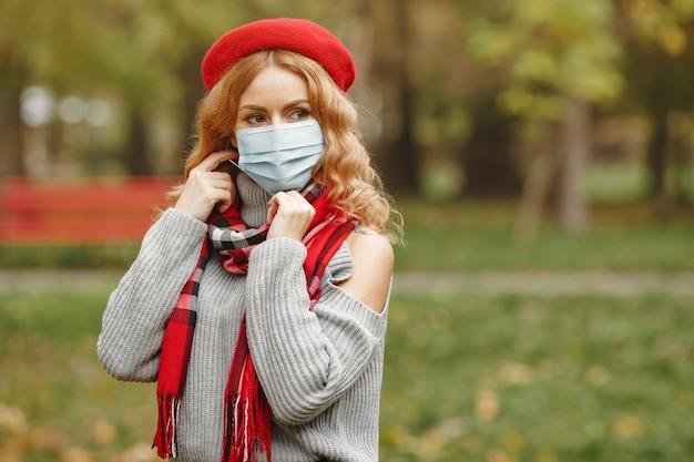 Frau im herbstwald. person in einer maske. coronavirus-thema. dame in einem roten schal. Kostenlose Fotos
