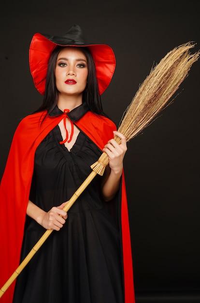Frau im hexenhut und -kostüm mit besen im halloween-festival Premium Fotos