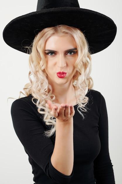 Frau im hexenkostüm, das einen kuss bläst   Premium-Foto