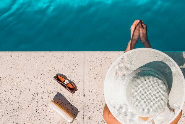 Frau im hut, der am rand des pools sitzt Kostenlose Fotos