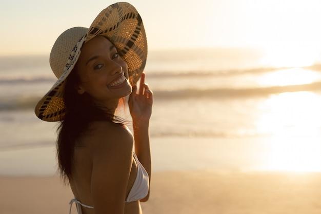 Frau im hut stehen am strand Kostenlose Fotos
