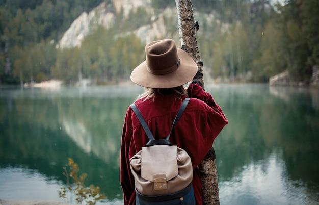 Frau im hut und im roten hemd nahe see in berge. Premium Fotos