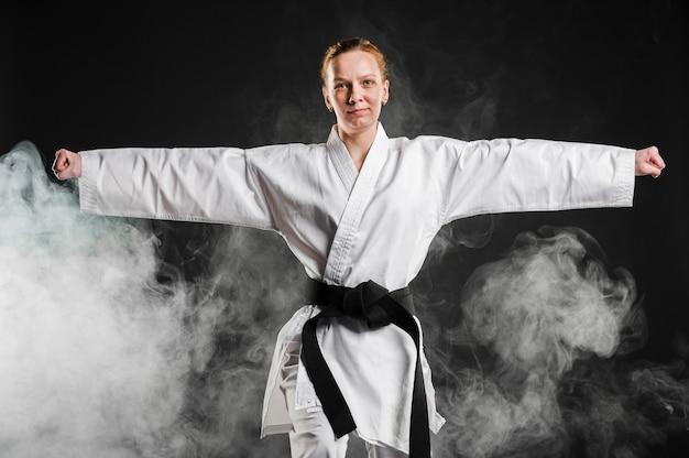 Frau im kimono, der taekwondo übt Kostenlose Fotos