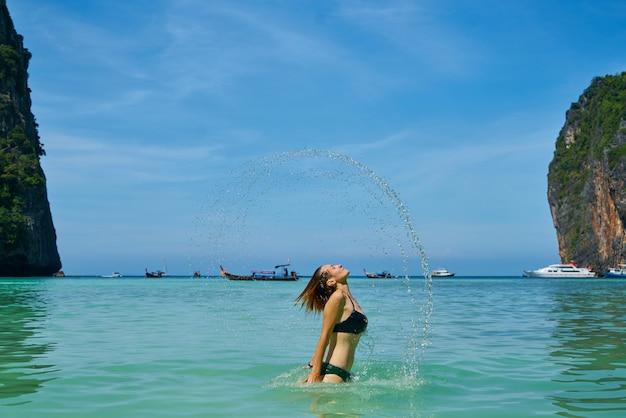 Frau im meer mit schöner landschaft Kostenlose Fotos