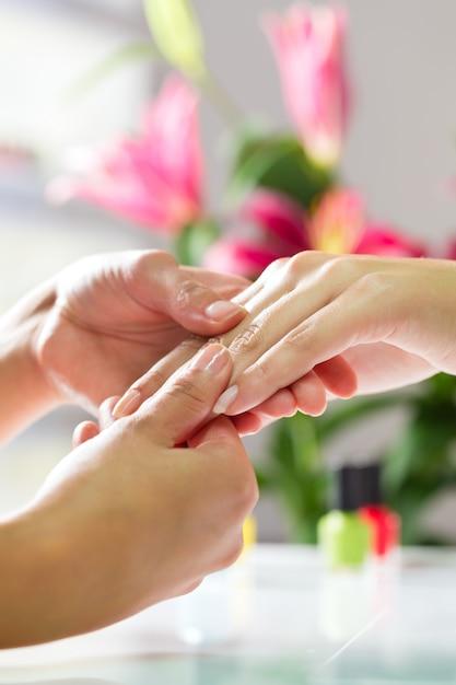 Frau im nagelsalon, der handmassage empfängt Premium Fotos