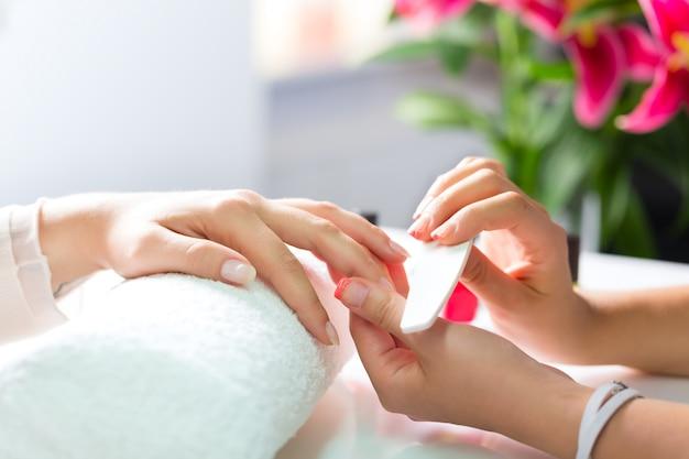 Frau im nagelsalon, der maniküre empfängt Premium Fotos