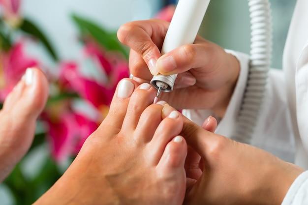 Frau im nagelstudio, das pediküre empfängt Premium Fotos