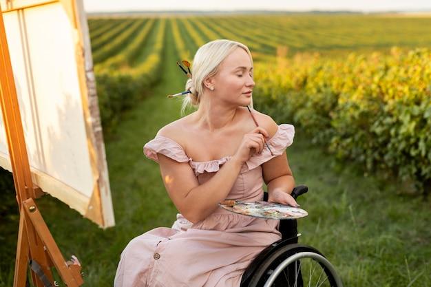 Frau im rollstuhl, der draußen malt Kostenlose Fotos