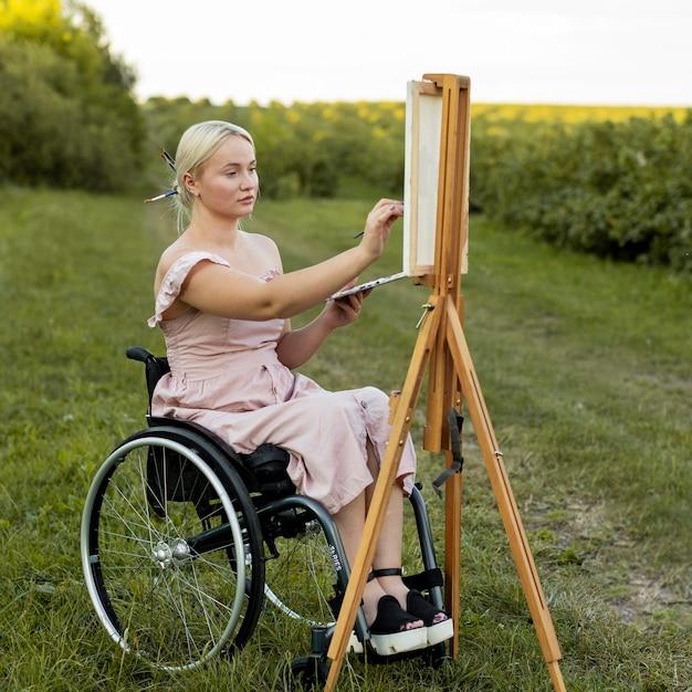 Frau im rollstuhl mit leinwand und palettenmalerei im freien Kostenlose Fotos