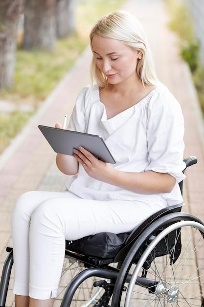 Frau im rollstuhl mit tablette außerhalb Kostenlose Fotos