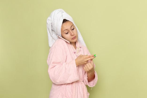 Frau im rosa bademantel, die am telefon spricht Kostenlose Fotos