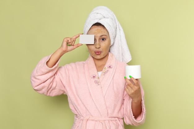 Frau im rosa bademantel hält weiße karte und creme Kostenlose Fotos