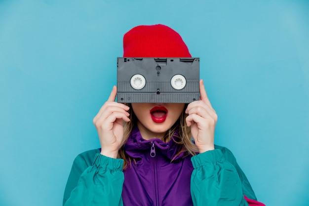 Frau im roten hut, sonnenbrille und anzug der 90er jahre mit vhs-kassette Premium Fotos