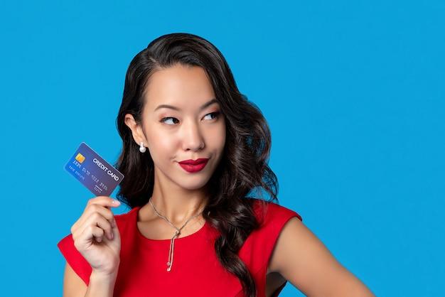 Frau im roten kleid, das in der hand kreditkarte zeigt Premium Fotos