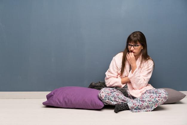 Frau im schlafanzug auf dem boden, der zweifel hat Premium Fotos