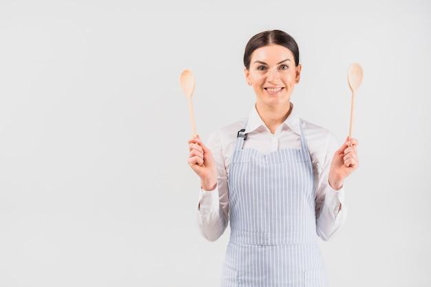 Frau im schutzblech lächelnd und löffel halten Kostenlose Fotos