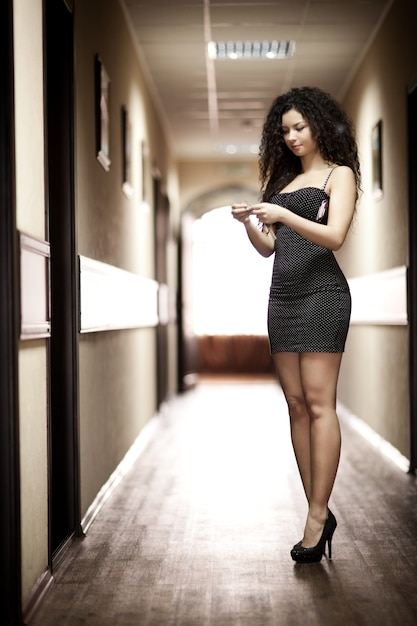 Frau im schwarzen kleid, das entlang korridor geht Premium Fotos