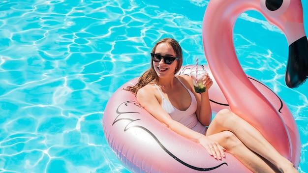 Frau im schwimmring ihr cocktail genießend Kostenlose Fotos
