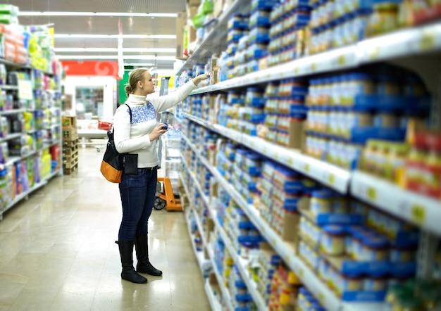 Frau im supermarkt. kinderessen. Premium Fotos