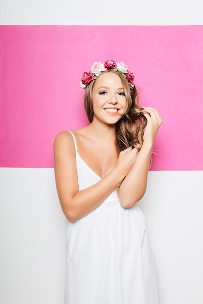 Frau im weißen baumwollkleid mit blumen beim haarlächeln Kostenlose Fotos