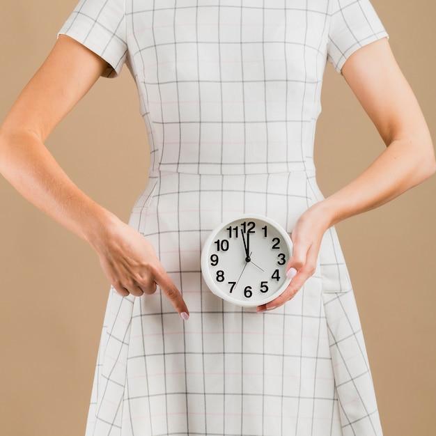 Frau im weißen kleid, das ihre menstruationsperiode zeigt Kostenlose Fotos