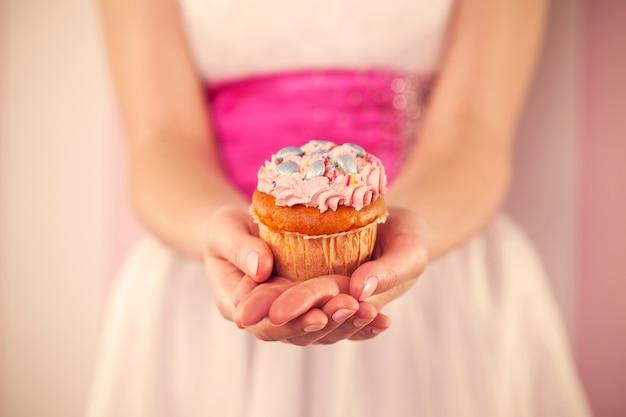 Frau im weißen kleid, das rosa muffin hält Kostenlose Fotos