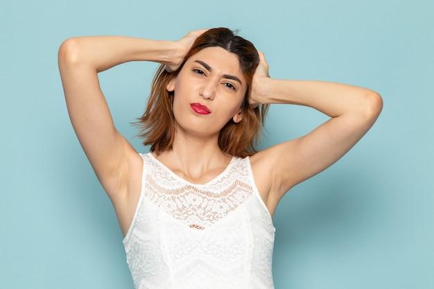Frau im weißen kleid posiert und hält ihre haare Kostenlose Fotos